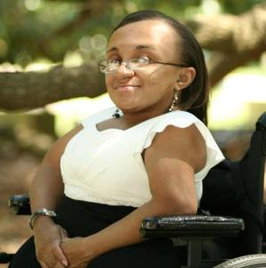 Photo of a young Black woman with her hair parted and hanging down straight.  She is smiling and facing the camera sideways in her wheelchair.  She is outside under the tree branches while wearing a white and black dress.