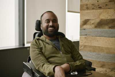 Photo of Srin Madipalli, a South Asian man with short black hair and a black beard. He is sitting in a power chair wearing an olive green hoodie. He is smiling at the camera.