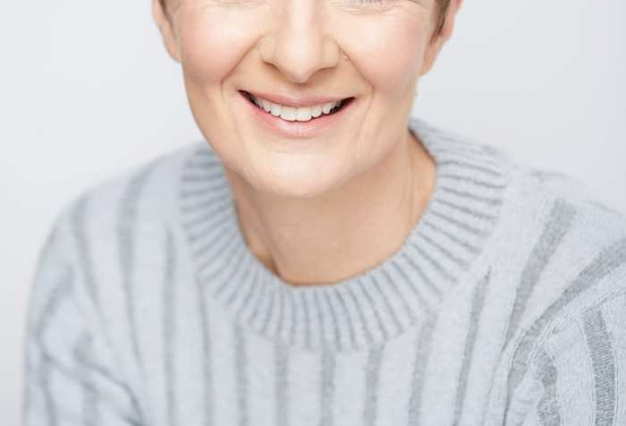A headshot of Pia Justesen a white Danish woman with short brown hear and wearing a light blue sweater.