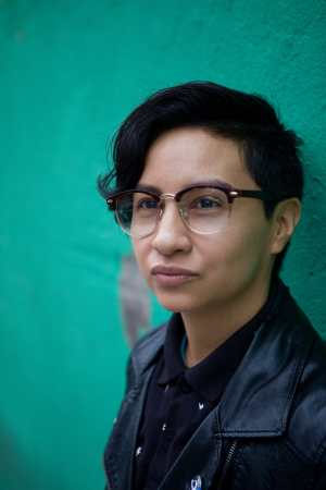 Image of a lightskinned Indigenous and white queer with short black hair, black-rimmed glasses, a button-up black polo, and a black pleather jacket leaning against a green wall and looking away from the camera. Image by Neha Gautam Photography.