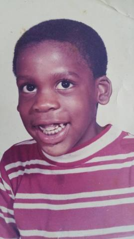 A young Black boy, Leroy Moore, with short black hair smiling at the camera. He is wearing a red and white striped shirt.