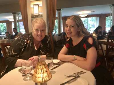 Two women with blonde hair smiling and posing for the camera at a table at a fancy restaurant in Harrison Hot Springs. On the left is Cathleen wearing a dark flower printed blouse and on the right is Amanda, the writer, wearing a black dress with roses on the sleeves. They look happy and rested.