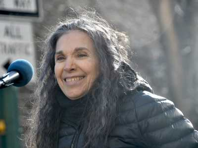 Photo of Nadia LaSpina, an Italian American woman with long curly gray hair with a microphone in front of her. She is wearing a black puffy jacket outdoors.
