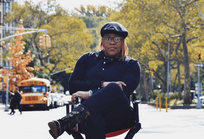 photo of Jade Bryan, a Black Deaf woman sitting in a director's chair outdoors with trees and parked cars behind her. She is wearing all black, and a black beret and glasses. Her left leg is crossed over her right, both arms folded.
