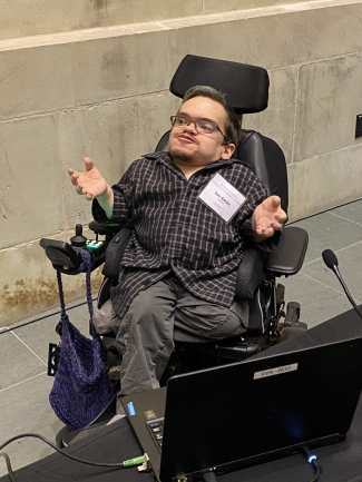 Ian is a white man in his 30s sitting in a power wheelchair with oene leg crossed under the other. He's spreading his hands and grinning, one eyebrow slightly raised, like he's gesturing mid-explanation. Nearby him is a laptop and a table with microphones.