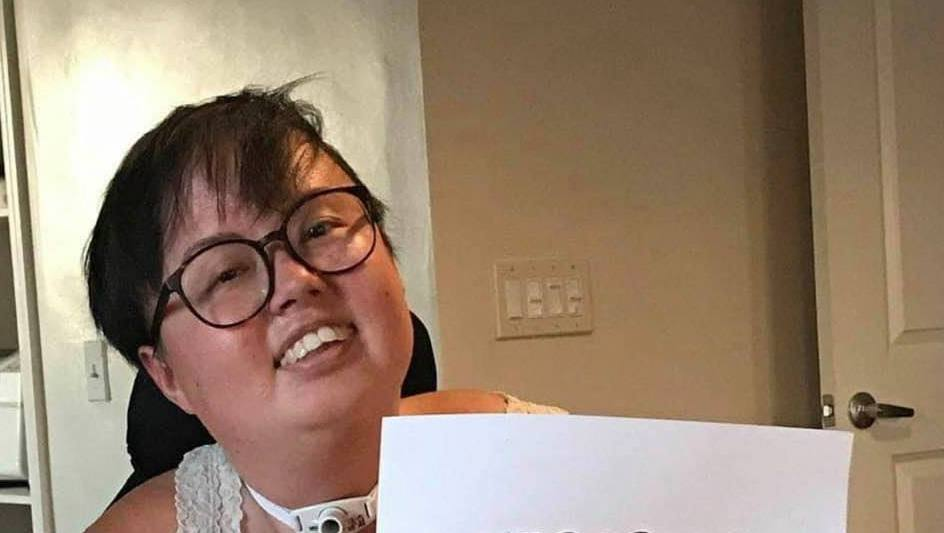 """A photo of Stacey Park Milbern, a mixed race Korean and white queer person, holding a paper sign that reads """"Cherished."""" The photo is stylistically torn at the edges with cursive text appearing across the bottom, """"Stacey Milbern."""""""