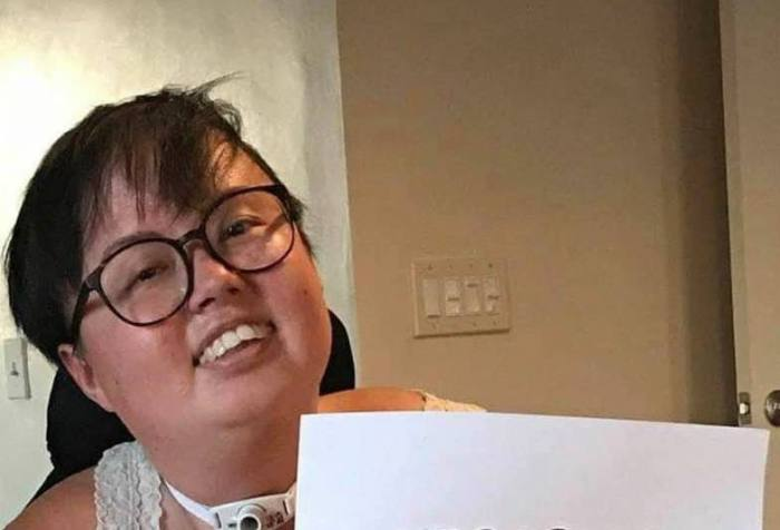 "A photo of Stacey Park Milbern, a mixed race Korean and white queer person, holding a paper sign that reads ""Cherished."" The photo is stylistically torn at the edges with cursive text appearing across the bottom, ""Stacey Milbern."""