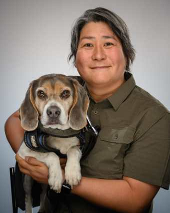 Photograph of Karen Nakamura (an asian american woman with short hair) holding her service dog Momo, a grey and white beagle. The photograph is studio quality.