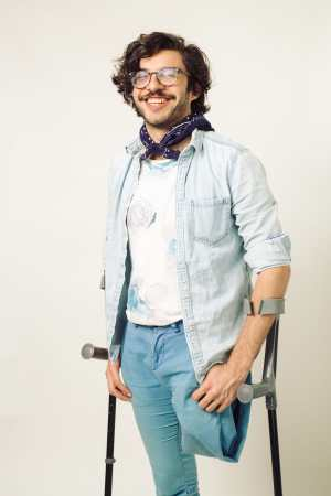 Alex, an above the knee amputee, poses joyously in a monochromatic light blue outfit and a dark blue bandana around his neck. Balancing on his crutches, he beams looking off into the distance with his dark brown, wavy hair framing his face.