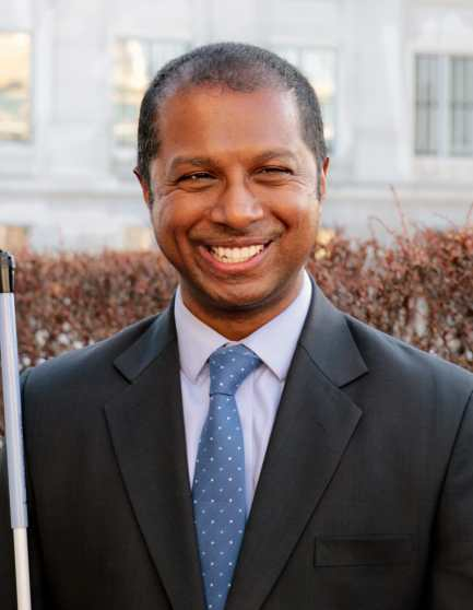 Picture of Sachin Pavithran, a South Asian man in a suit holding white cane outside the Capitol in Salt Lake City.