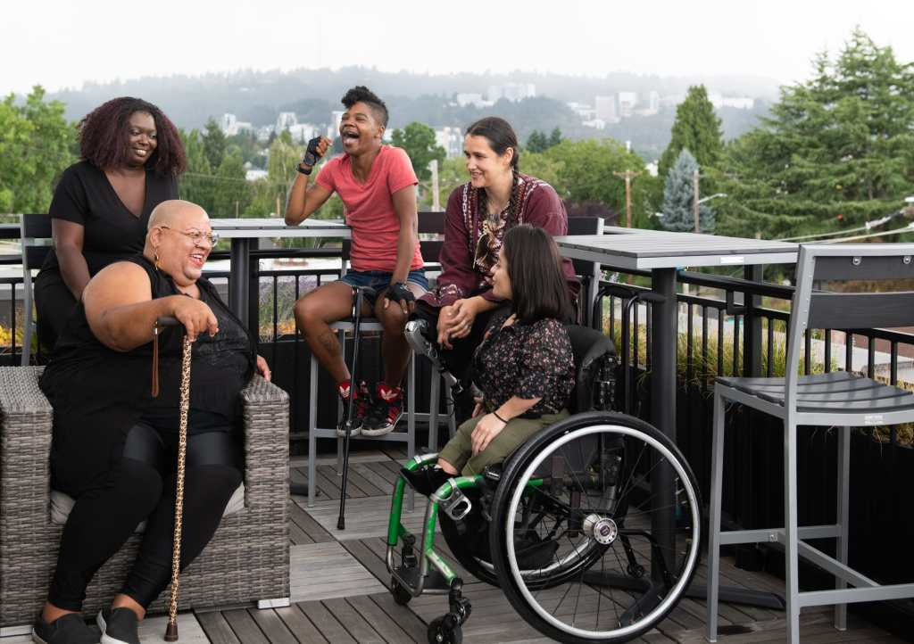 Five disabled people of color with canes, prosthetic legs, and a wheelchair sit on a rooftop deck, laughing and sharing stories. Greenery and city high-rises are visible in the background. Photo credit: Disabled and Here https://affecttheverb.com/disabledandhere/