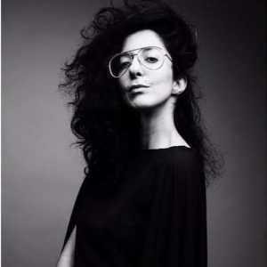 A black and white photo by photographer John Midgeley, featuring Porochista Khakpour in all black with long curly hair and glasses.