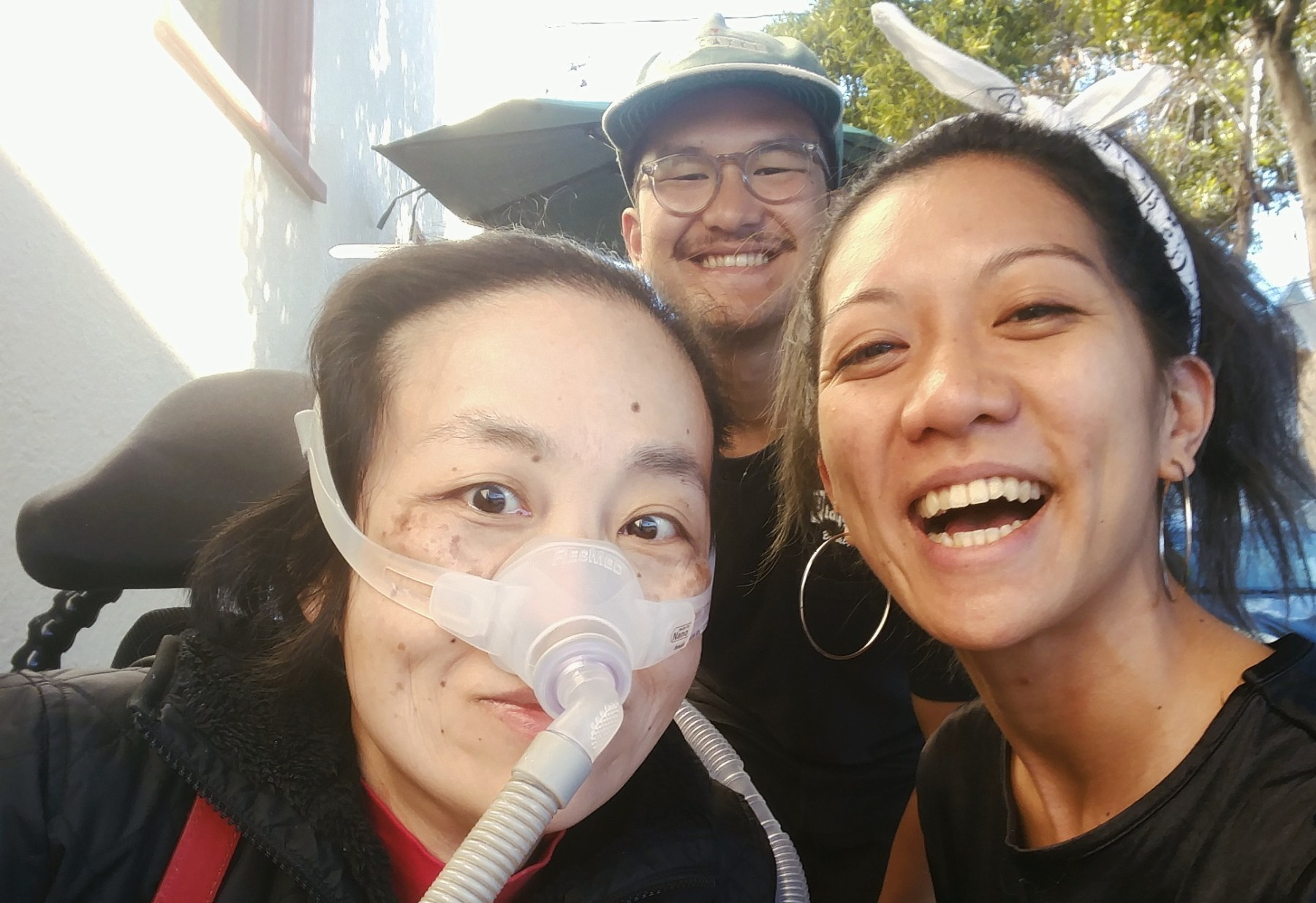 Three Asian Americans taking a selfie at an outdoor sidewalk. In the back is Luigi Villanueva, on the left is Alice Wong, a wheelchair user with a mask over her nose attached to a ventilator, on the right is Rochelle Kwan. Everyone is smiling.