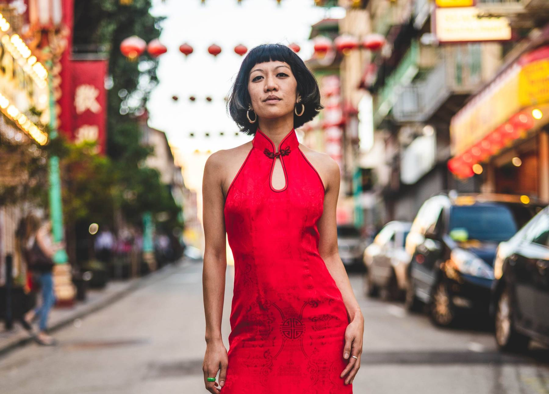 Rochelle Kwan, a Chinese-American woman with short black hair, stands in the middle of a San Francisco Chinatown street looking down at the camera with a soft smile. She wears a long, red cheongsam dress, black boots, gold hoop earrings, and a jade ring. In the background are rows of hanging red lanterns, neon signs with Chinese characters, and parked cars. This photo was taken by her sister, Elodie Kwan.