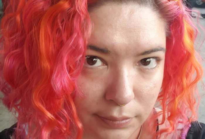 Headshot of a Light skinned indigenous non-binary person with short bright pink and orange hair. She has brown eyes and a septum piercing. She is wearing a pink striped shirt with a black cardigan over top. She has two heart tattoos on her collar bones.