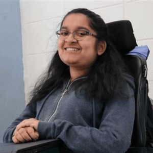 A South Asian woman with light brown skin, dark eyes, and black glasses smiles at the camera. She is sitting in an electric wheelchair with a purple jacket tucked behind the headrest, her hands folded over a Chromebook that rests on a wheelchair tray. Behind her is a white brick wall that gives way to untextured blue on the left of the image.