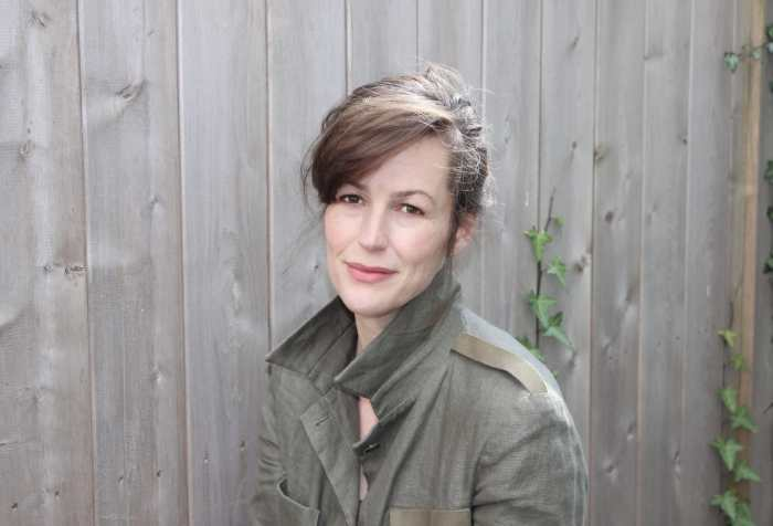 Sara Hendren, a white middle aged woman with brown hair and brown eyes, sits in front of a weathered wood fence, wearing an olive linen jacket.