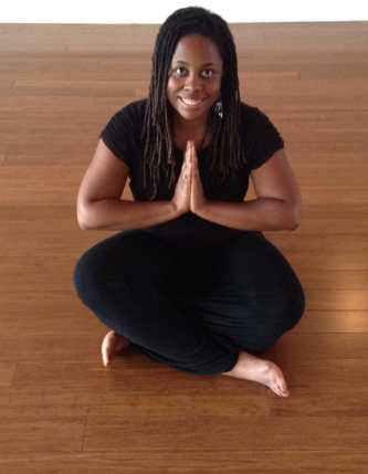 IMAGE OF MIXED ABILITIES DANCE TEACHER INDIA HARVILLE. SHE IS AFRICAN-AMERICAN WITH HAIR IN LOCKS, WEARING ALL BLACK, SITTING ON THE FLOOR WITH HER HANDS CLASPED, SMILING AT THE CAMERA.