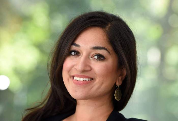 Jaipreet Virdi, a South Asian woman with dark hair, smiles at the camera. Her head is slightly turned. She is wearing a black blazer and dark top. There are some trees in the blurred background.