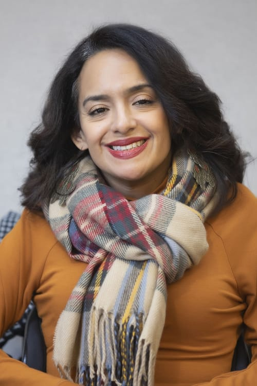 a photo of Ligia Andrade Zúñiga, a woman color with a disability smiling, she has long wavy hair, is wearing a scarf, and has long dangly earrings.