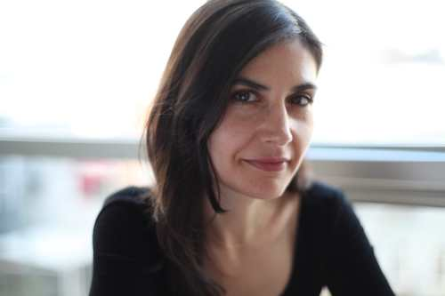 Alexis, a white woman with long dark hair, sits inside in front of a window. She is wearing a long sleeved black shirt and smiles softly at the camera.