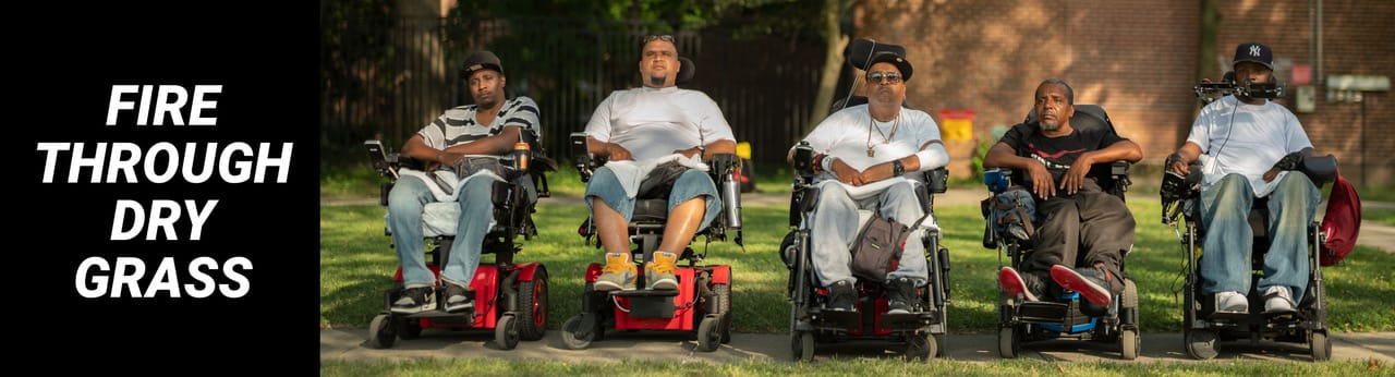 Five Black and brown men (from left to right: Vince, Jay, Tito, Pete and Var) sit in wheelchairs outside, all lined up in a straight horizontal line facing the camera. They wear T-shirts and sneakers and some wear baseball caps. They all look into the camera with serious expressions. Photo credit: Elias Williams