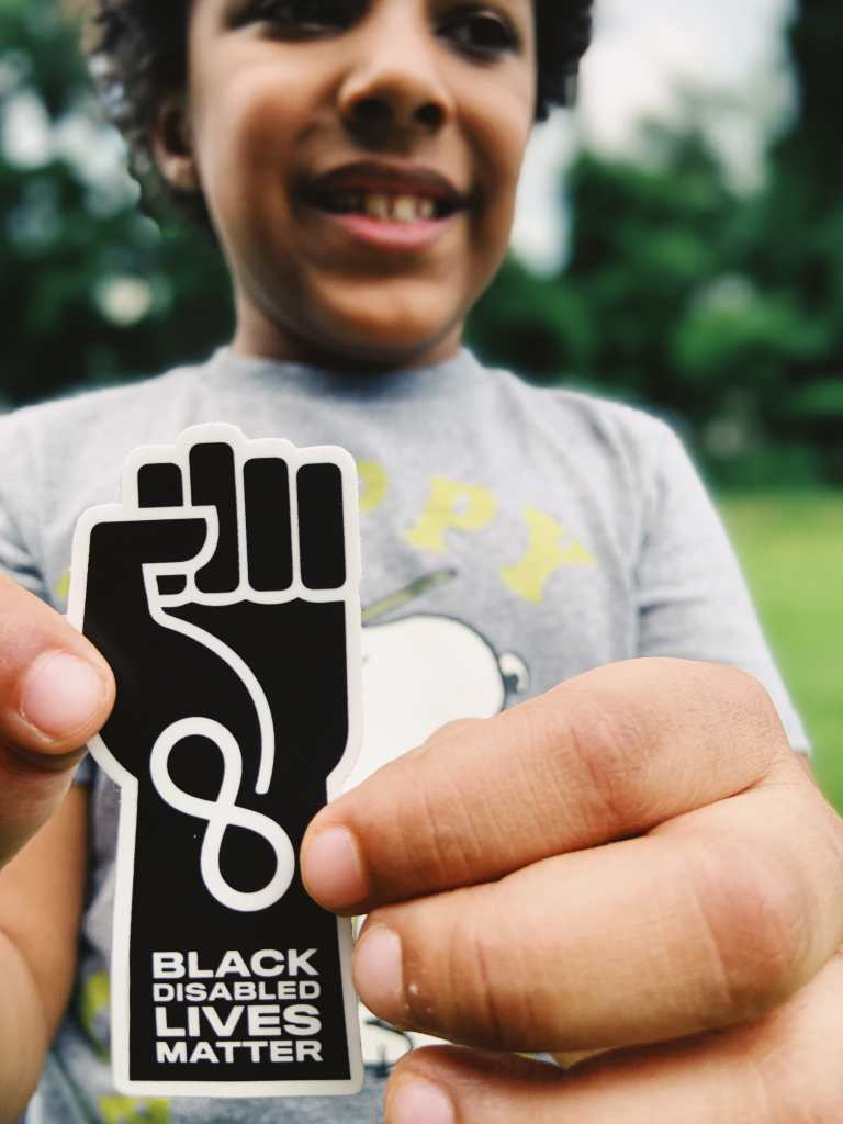 Photo of Knox White-Johnson, a Black Autistic boy smiling and holding a sticker designed by his mother, Jen White-Johnson, an illustration of a raised solidarity fist in black with an infinity symbol at the wrist in white with the words 'Black Disabled Lives Matter' below.