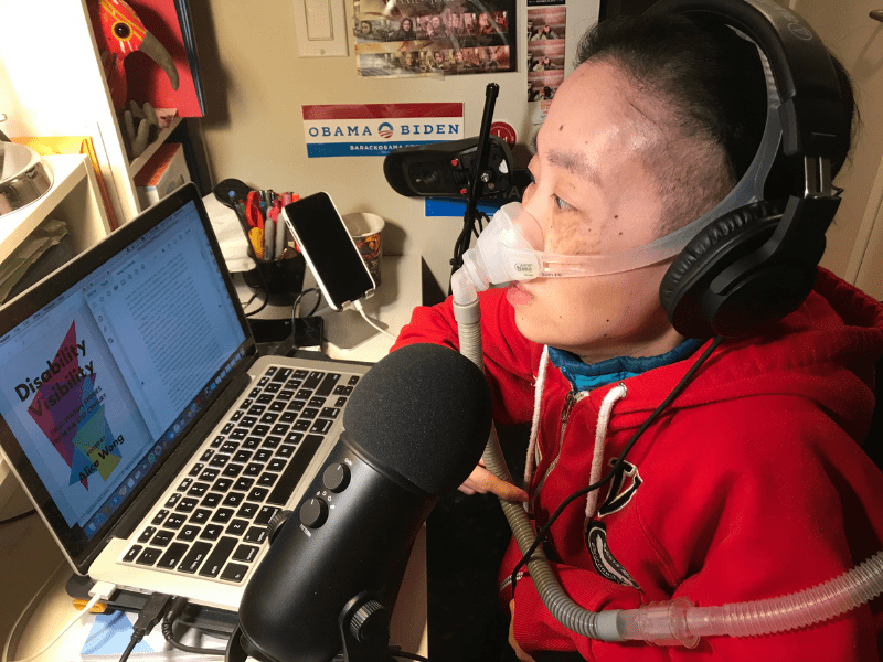 Photo of Alice Wong, an Asian American woman in a wheelchair at her desk with a laptop open. She is wearing a red hoodie and headphones over her ears. There is a mask over her nose attached to a ventilator. Next to the laptop is a microphone.