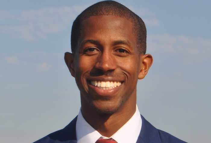 Dr. Justin Bullock, a Black man with short hair wearing a navy suit with a white shirt and dark red tie. He is smiling at the camera.