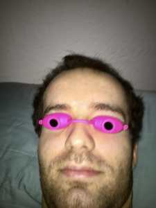 A photo of Jamison Hill, a young white man with short brown hair and a half-grown beard. He is lying in bed wearing hot pink tanning goggles over his eyes that aid him in his writing.