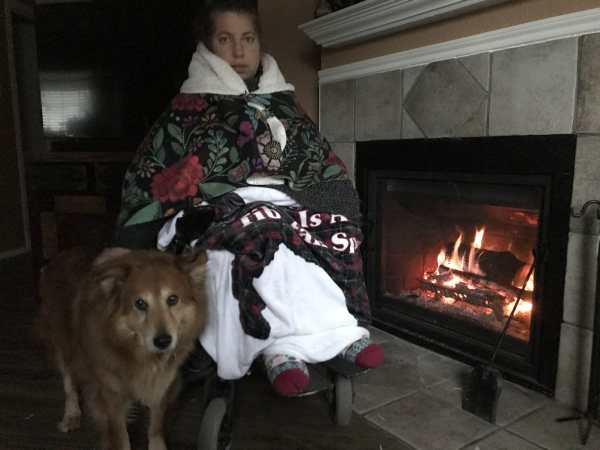 Day 2: Emily Wolinsky sits still next to her fireplace in a dark room. She's covered in blankets of different colors and patterns. She has thick socks on her feet. Her dog, Byron, a fluffy sweet poof, sits next to her.
