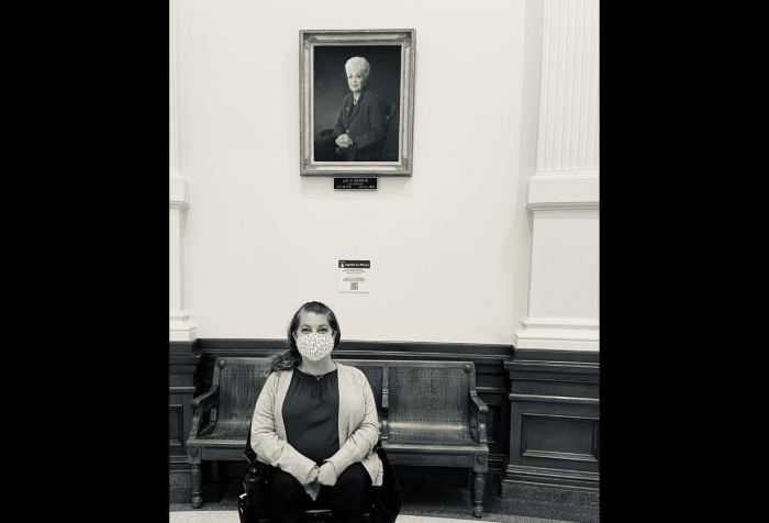 Graphic with a black background and in the center is a black and white photo of Emily Wolinsky sitting in her power wheelchair in front of a portrait of the late Governor of Texas, Ann Richards.