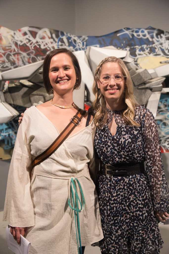 Photo of curators Vanessa Chang and Lindsey D. Felt standing shoulder to shoulder in front of a graffiti installation, beaming at the camera. Lindsey has wavy blonde hair and wears translucent glasses and a gauzy black and white dress with a black double buckle belt. Vanessa has a short dark brown bob and wears a gold choker necklace and a long sleeved white kimono top. A brown bag strap crosses her chest.