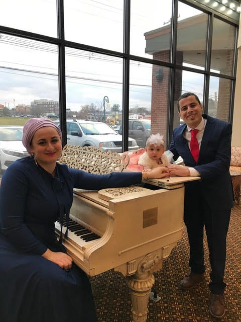 Photo of three people gathered around a white grand piano. On the left sitting on the piano bench, Nazli Khazirova, a woman with a purple head covering and a navy blue outfit smiling widely. Her arm is extended toward Mustafa Rfat on the right, a man wearing a navy blue business suit with a white shirt and red tie who is also smiling. In the center, laying on top of the piano is Defne Rfat, a little baby girl with a white flower-like headband and a white and pink tulle outfit like a ballerina