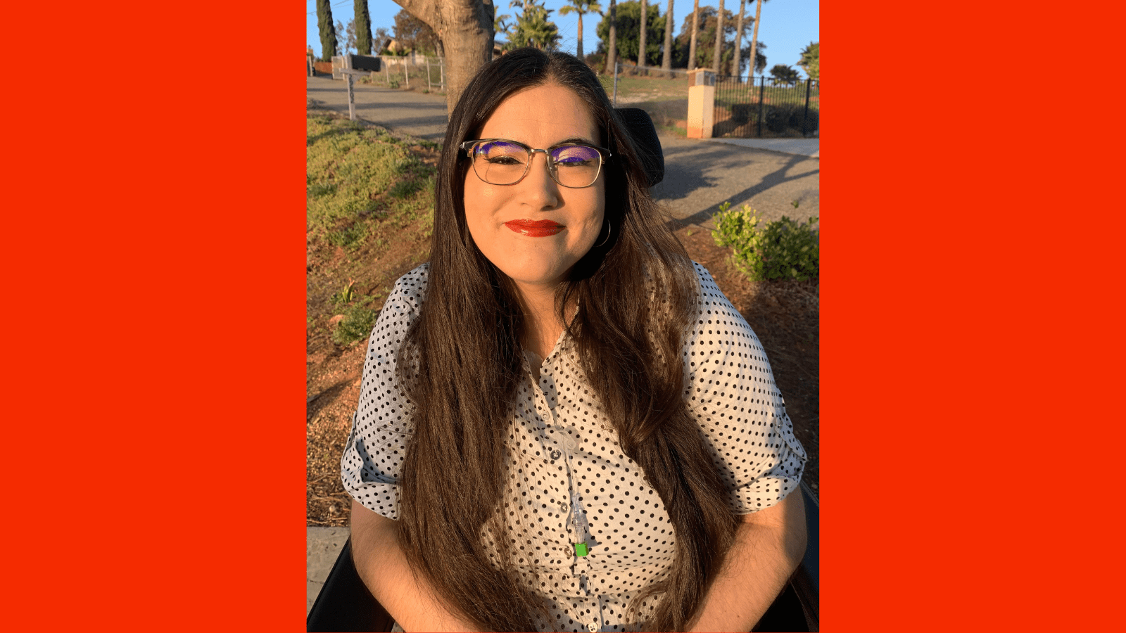 Graphic with a red background with a photo of Alena Morales, a Mexican Filipina woman, sitting in her wheelchair among San Diego palm trees. Her long brown hair is styled down around her shoulders, and she dons red lipstick with winged eyeliner. She is wearing a white button up shirt with black polka dots, and her central line hangs out from the neckline of her shirt.