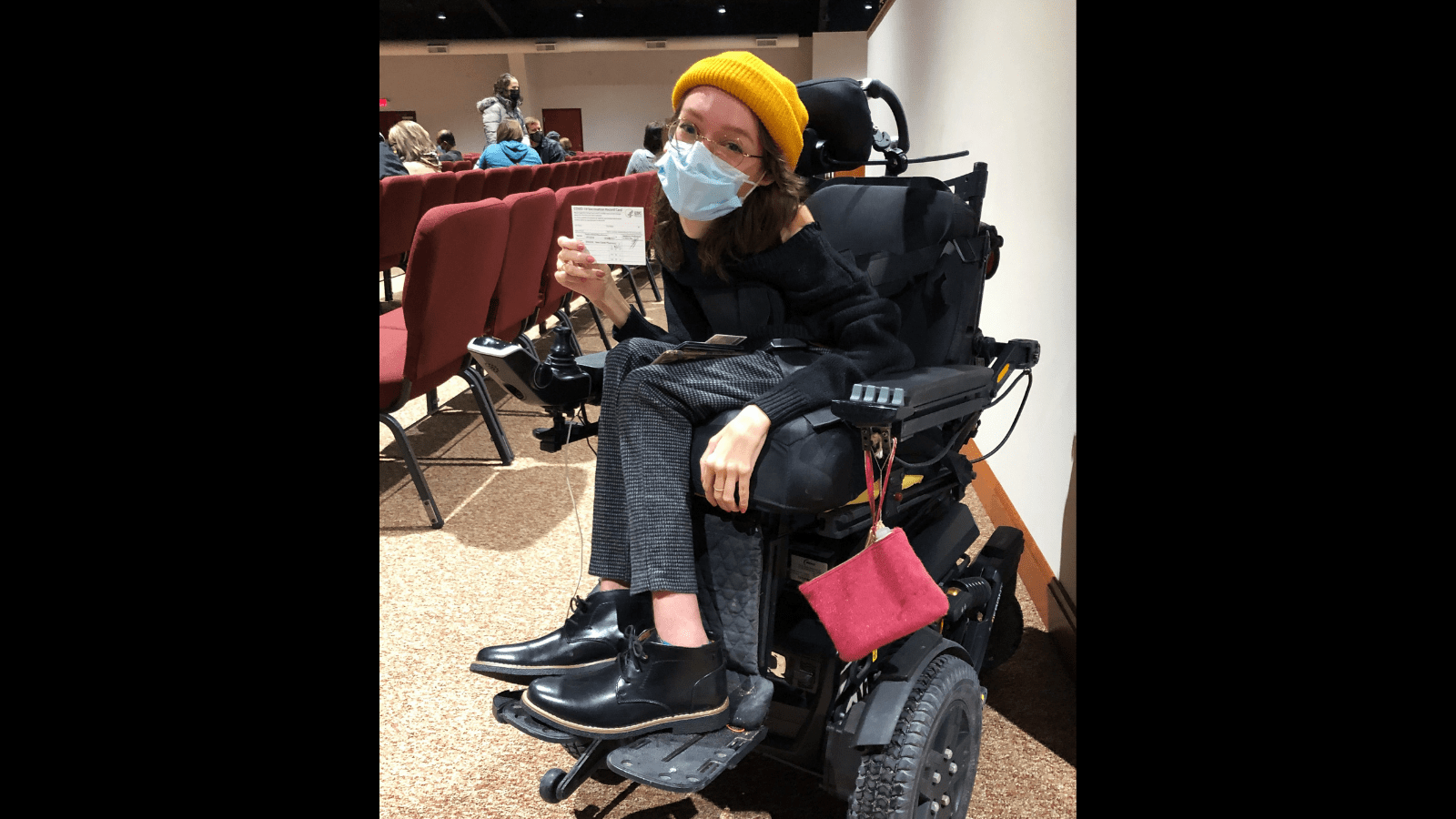 Graphic with a black background and a photo of Emily Ackerman, a white woman in a black power wheelchair is holding up her COVID vaccine card. She's wearing a black sweater and boots with grey checked pants, a yellow beanie, and a blue medical mask.