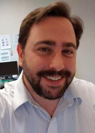 Gregg Beratan, a white man with brown hair and a brown beard. He is smiling and wearing a white shirt with narrow gray stripes.