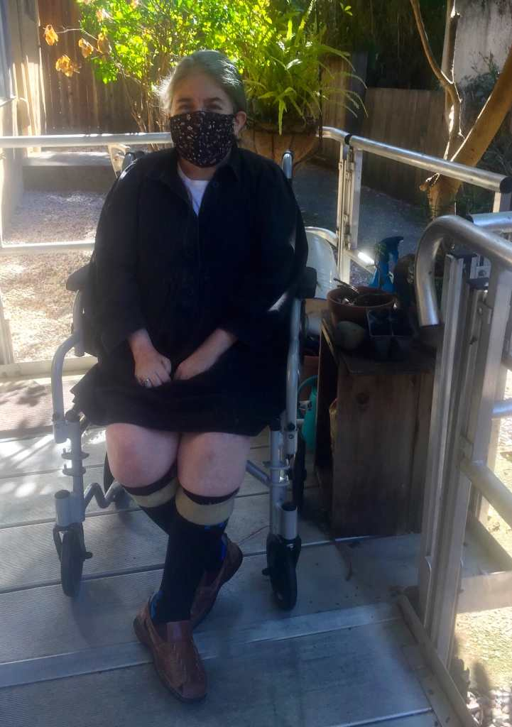 Five weeks later. The same woman, Ingrid Tischer in a cloth mask and shoe orthotics sitting outside in a transport chair on a ramp in the sun.