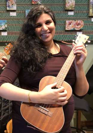 A brown woman with long, curly, black hair, stands smiling while playing a ukulele. She is visibly pregnant, wearing a dark purple dress. The background shows a green wall with small paintings of flowers hanging.