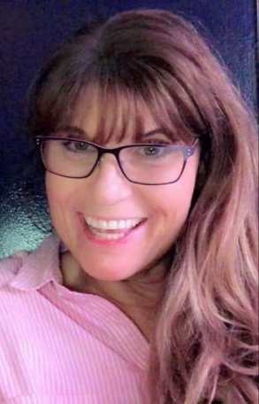 A headshot showing Sharon with long brown hair, wearing large square glasses, looking directly at the camera and smiling. They are wearing a light pink collared shirt.