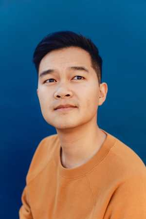 Jonny Sun, a young Chinese Canadian man with short black hair wearing an orange crewneck shirt. He is looking upward at the sky pensively. There is a deep blue background behind him. Photo credit: Rozette Rago