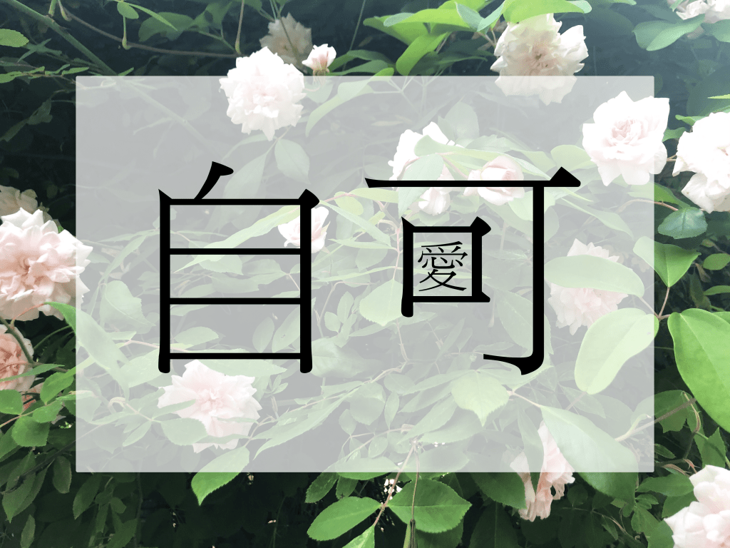 The Chinese character for self (自/zì) and the character in can (可/kě) with the traditional Chinese character for love (愛/ài) inside the character for mouth (口/ kǒu). The letters are black and are centred on a translucent white inset rectangular background in front of a background of an abundant bush of leaves and pink-white roses.