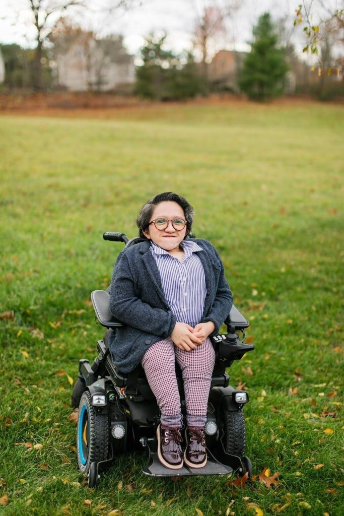 This is a photo of Sandy Ho sitting in her power wheelchair in the middle of a field of green grass, with houses blurred in the background. She has short darkwavy hair and tortoise shell glasses on. Sandy is wearing maroon shoes, plaid pants, a dark gray cardigan, and a button-up blue and white striped collar shirt. She is smiling at the camera with her hands in her lap.