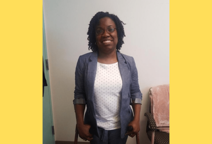 Graphic with a yellow background featuring a photo of a Black woman with curly natural, black hair and glasses in a blue chambray suit and white and blue polka dot top standing on crutches in an office.