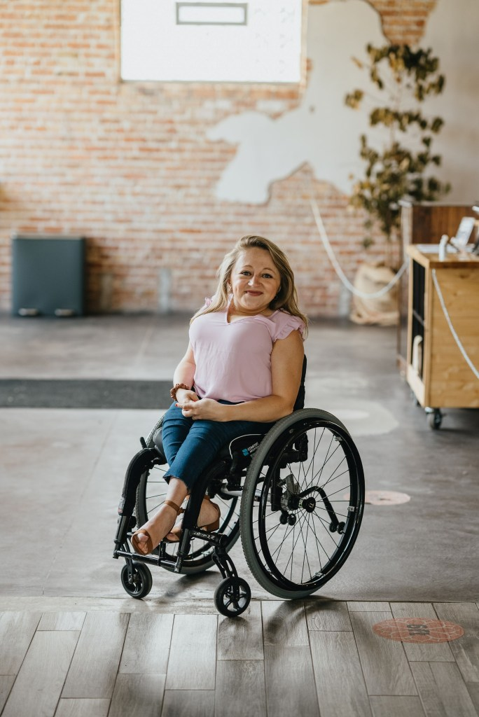 A white woman, Emily, with blonde, shoulder-length hair sits in a black wheelchair. She is short of stature. She is wearing a pink short-sleeved shirt and blue jeans with brown wedge heels. The ground is partially cement, partially wood. There is a brick wall behind her.