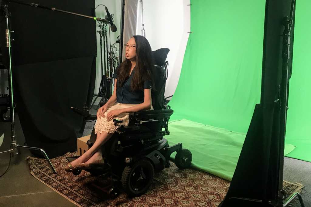 Aubrie on a film set in front of a green screen and with a boom mic pointed at her. She wears a teal blouse, white lace skirt, and black glasses. She rides a power wheelchair.