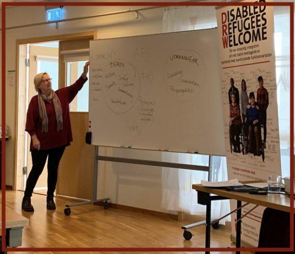 Riitta Lenna Karlsson framför ett tavla där det står lösningar för de utmaningarna som finns inom mottagandet av nyanlända inom kommunen