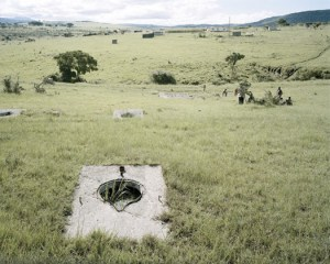 "Remains of long-drop lavatories built for the ""closer settlement camp"" of Frankfort, Eastern Cape. The 5,000 members of the black farming community of Mgwali were to have been forcibly removed and resettled here after their land was declared a ""black spot"" by the apartheid government in 1983. However, the people of Mgwali resisted strongly and in 1986 the removal scheme was dropped. The lavatories were gradually stripped of their usable building materials by people in the area and all that is left now are concrete bases over some 1500 anatomically shaped holes in the veld. 22 February 2006. Photo and text by David Goldblatt"