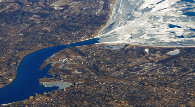 Aerial view of Highway 402 passing through Sarnia. The Blue Water Bridge is visible, and Lake Huron can be seen at the top of the image, still frozen. Image: WikiCommons.