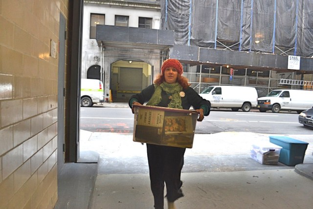 Librarian carrying books into Norm's office. (photo: M. Oman-Reagan)